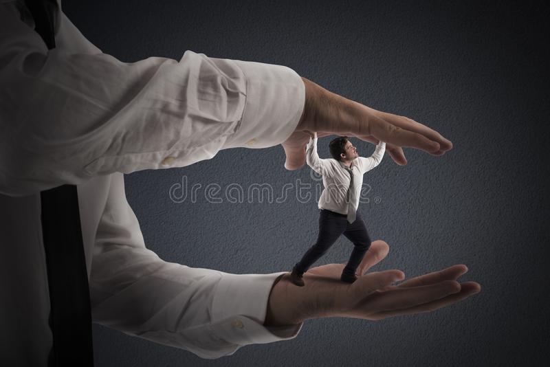 Oppressed by boss. Big hands that crush a small man royalty free stock images