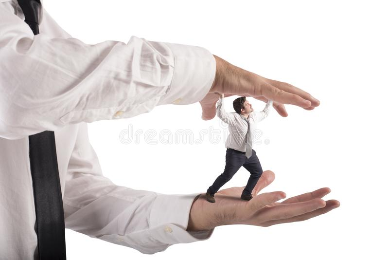 Oppressed by boss. Big hands that crush a small man royalty free stock photography