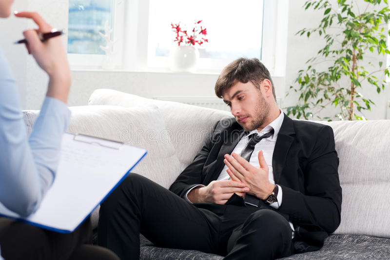 Oppressed man talking with psychologist stock images