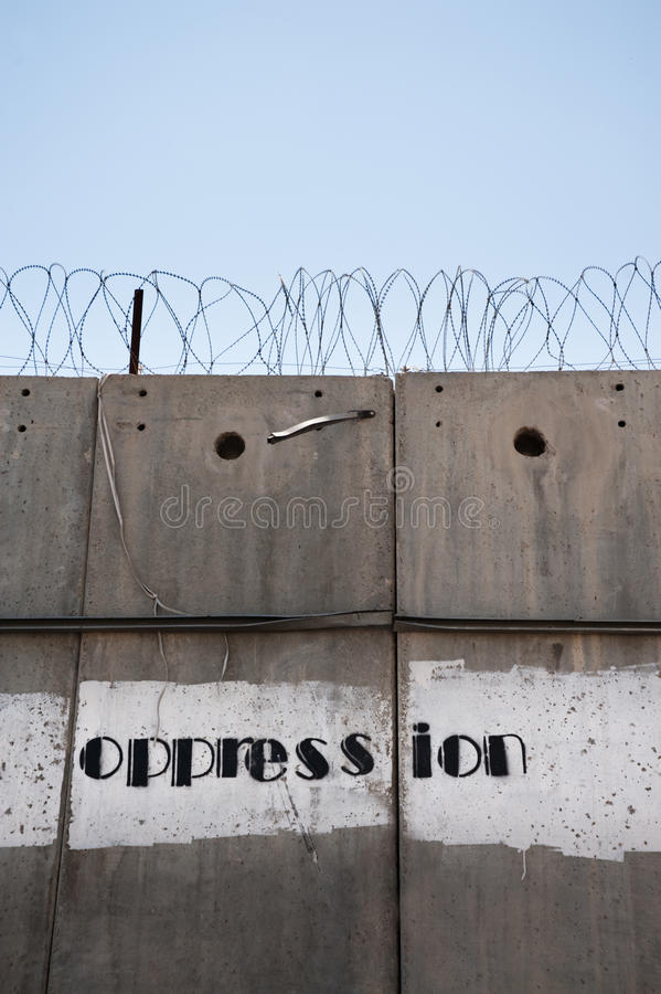 Oppression: The Israeli Separation Wall. Stencilled graffiti reading oppression is painted on the Israeli separation wall isolating the Palestinian neighborhood stock photo