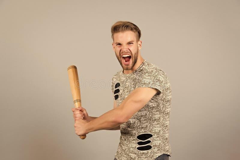 Opprima il fronte aggressivo gridante dell'uomo, fondo grigio Uomo con il pipistrello di legno pronto ad attaccare Concetto aggre fotografie stock