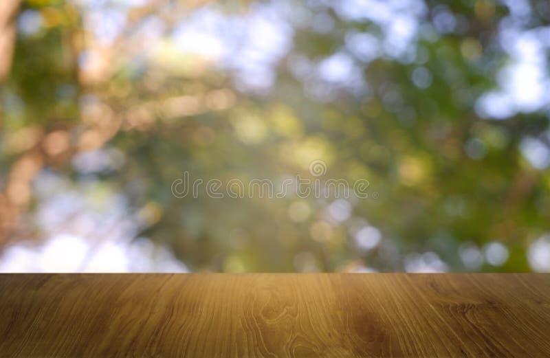 Opróżnia drewnianego stół przed abstrakt zamazującą zielenią ogródu i natury lekki tło Dla montażu produktu projekta lub pokazu zdjęcia royalty free