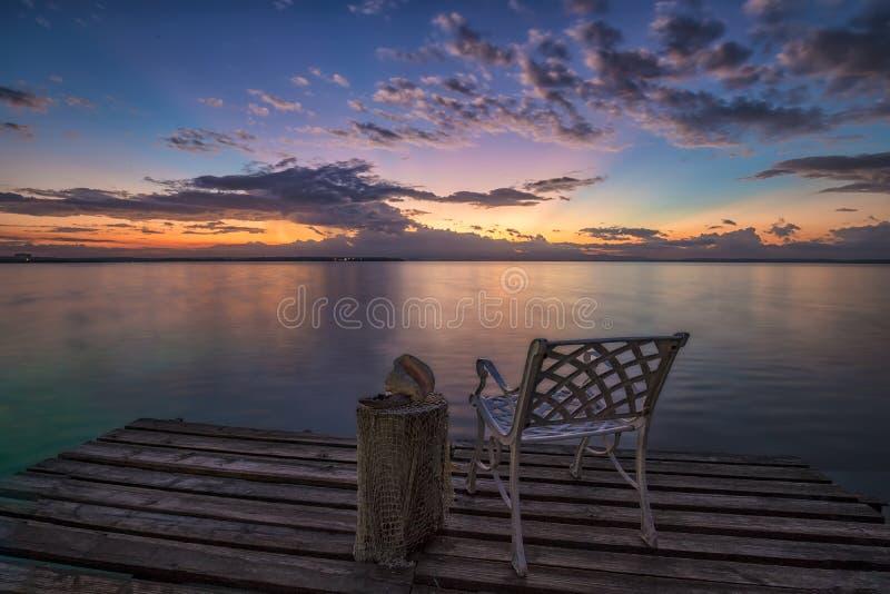 Opróżnia krzesła czekać na wschód słońca na drewnianym molu zdjęcie royalty free
