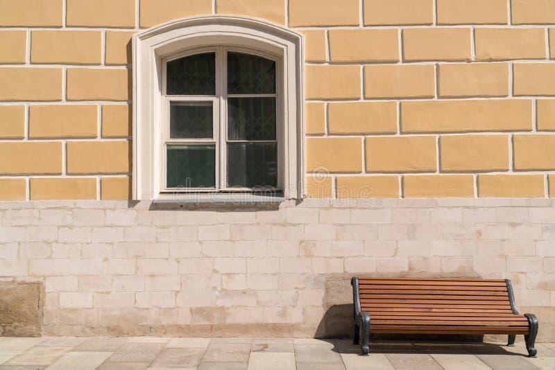 Opróżnia ławkę przeciw ścianie z okno obrazy royalty free