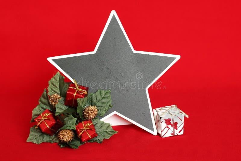 opróżnia łupek w postaci gwiazdy pisać wiadomości na czerwonym tle z czerwonymi i białymi prezentami umieszczającymi na wianku jo obrazy royalty free