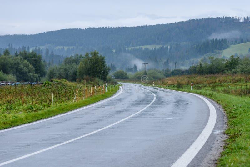 opróżnia asfaltową drogę w wsi w jesieni obraz royalty free
