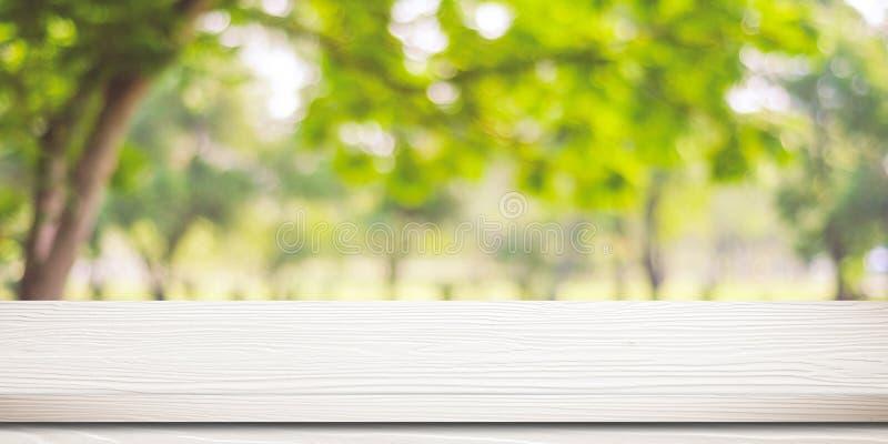 Opróżnia białego drewno stół nad zamazanym drzewem z bokeh tłem, zdjęcia stock