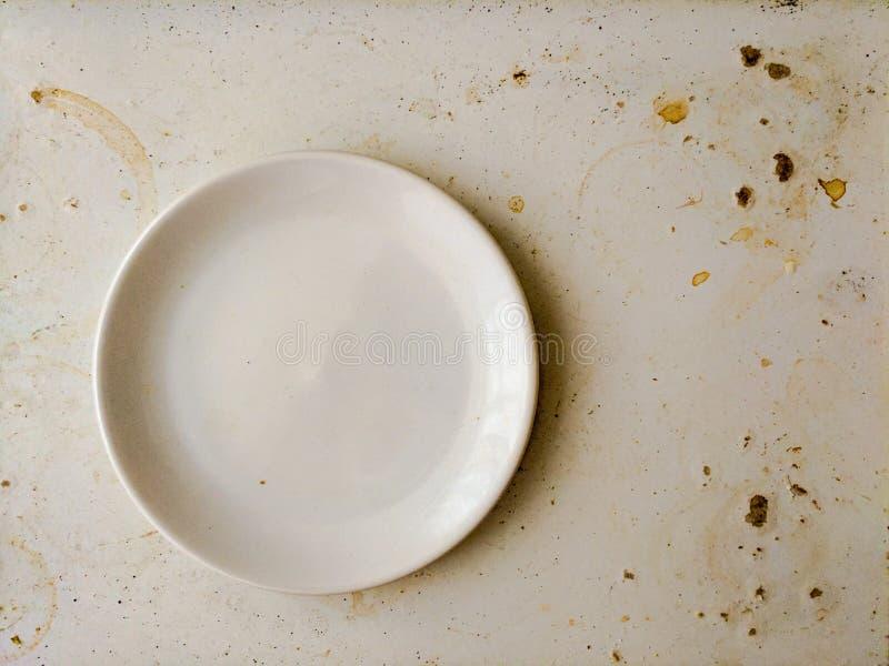 Opróżnia bielu talerza na brudnej pobrudzonej desce Otarcia pojęcie obraz stock