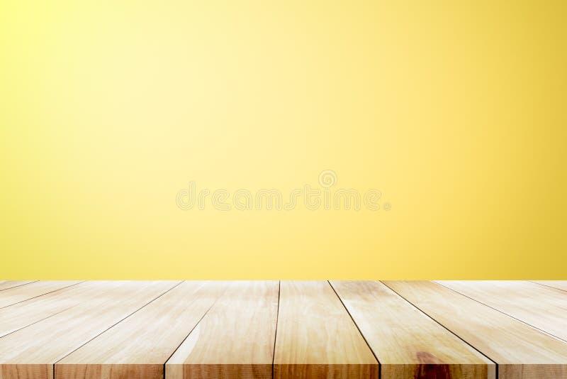 Opróżnia drewnianego pokładu stół nad żółtym tapetowym tłem zdjęcie royalty free