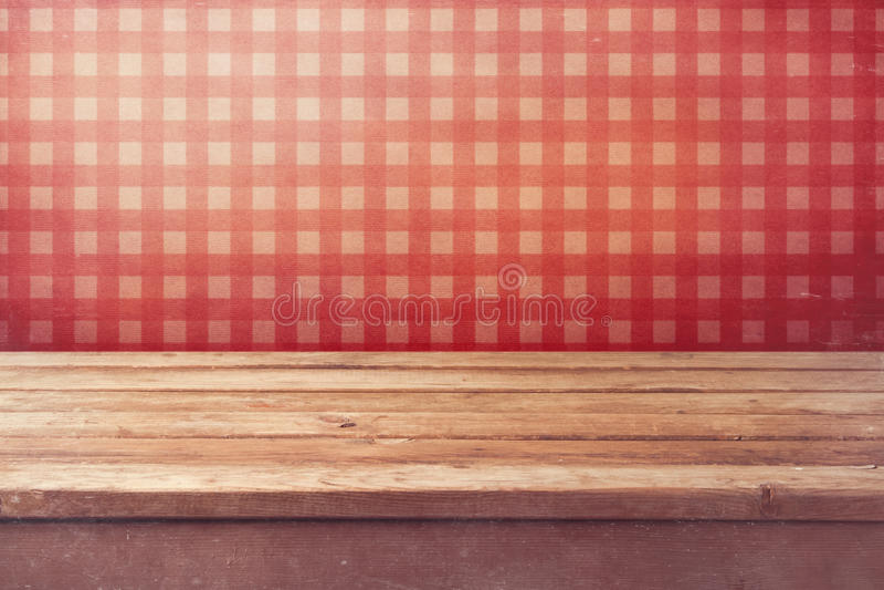 Opróżnia drewnianego pokładu stół nad sprawdzać czerwoną tapetą Rocznik kuchni wnętrze zdjęcia stock