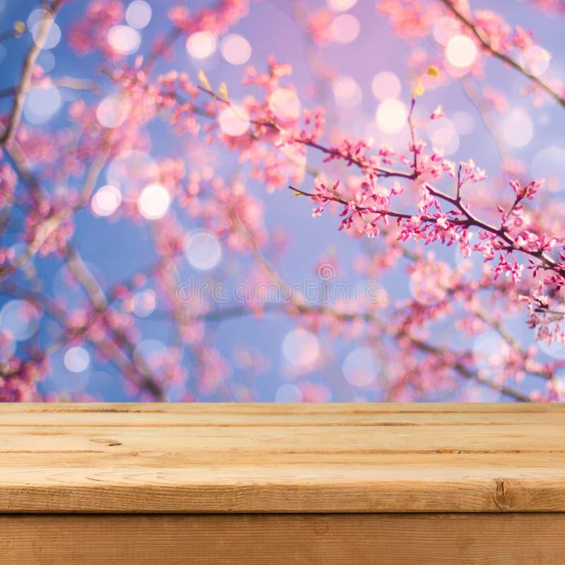 Opróżnia drewnianego pokładu stół nad zamazanym bokeh wiosny ogródu tłem obraz royalty free