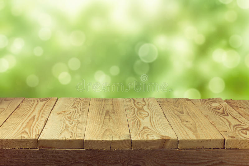 Opróżnia drewnianego pokładu stół z ulistnienia bokeh tłem Przygotowywający dla produktu pokazu montażu zdjęcie stock