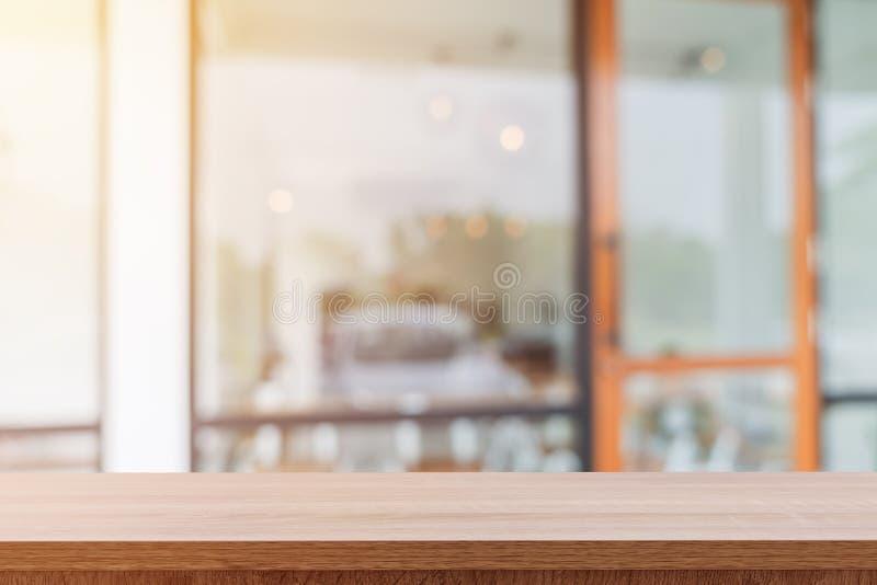 Opróżnia drewnianego stół i zamazujących ludzi w sklep z kawą tle, zdjęcia stock