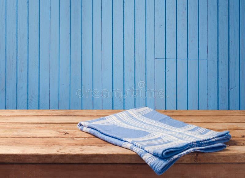 Opróżnia drewnianego stół z tablecloth nad błękitnym drewno ściany tłem Tło dla artykułu żywnościowy pokazu montażu zdjęcie stock