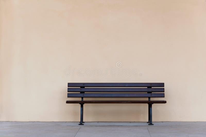 Opróżnia drewnianej ławki krzesła przeciw pustej ścianie obraz stock