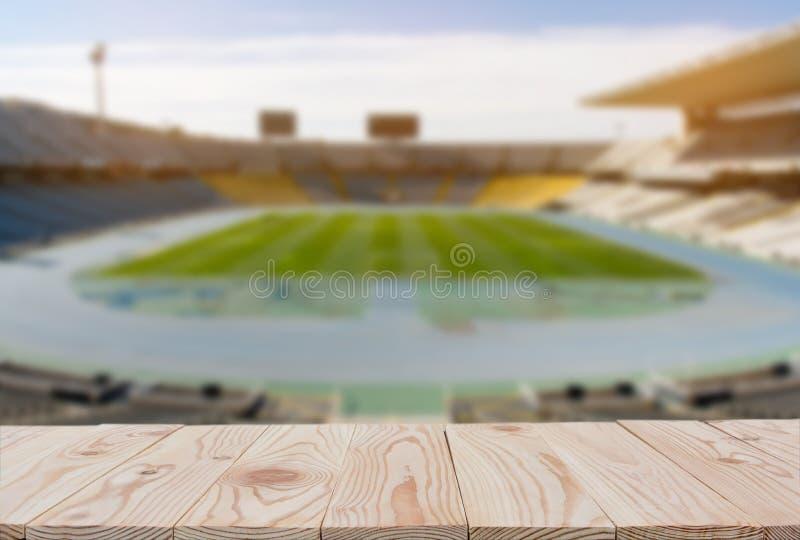 Opróżnia drewnianej deski stołowego wierzchołek zamazany futbolowy boiska do piłki nożnej tło dalej z kopii przestrzenią dla poka zdjęcia stock