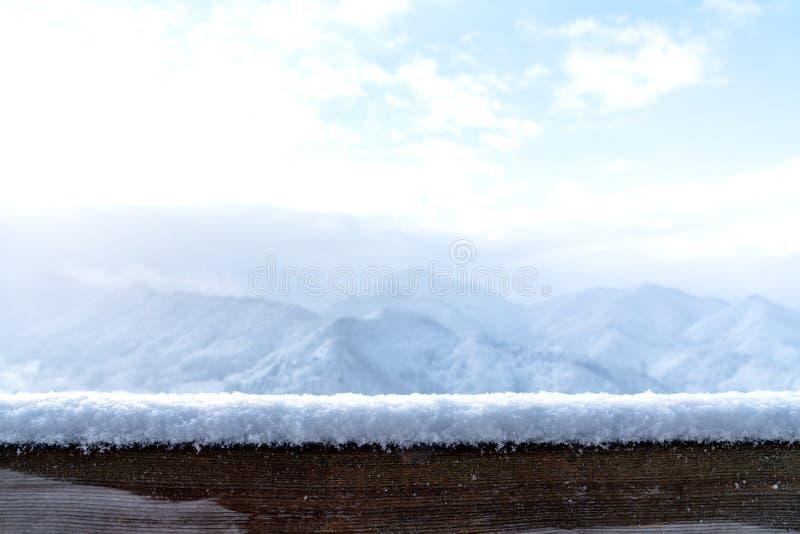 Opróżnia Drewnianej deski wierzchołka stół przed zamazanym śnieżnym widoku górskiego tłem Perspektywiczny drewno w zamazanym zima zdjęcia stock