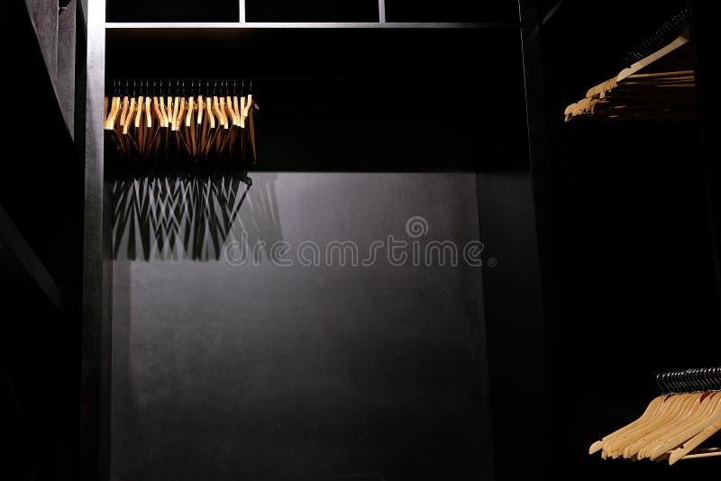Opróżnia drewnianych odzieżowych wieszaki wiesza w szafy i kastingu cieniach głęboko obrazy royalty free