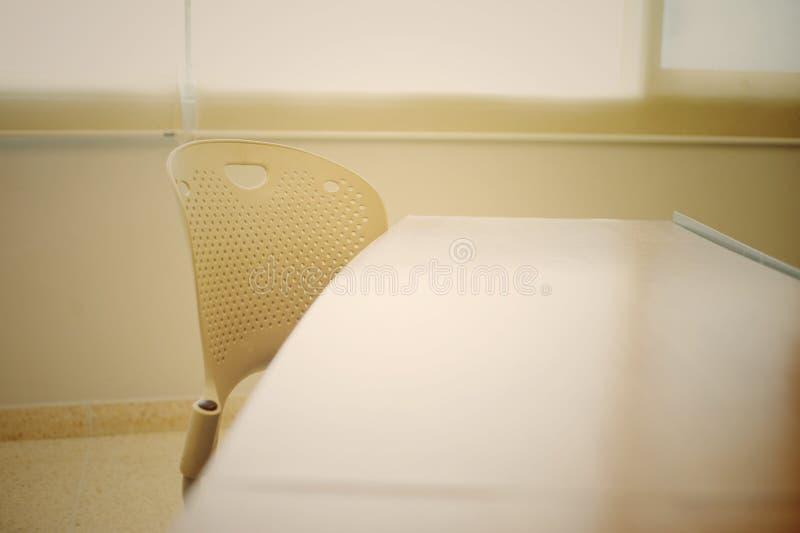 Opróżnia krzesła i stołu w sala lekcyjnej z ciepłym światłem od outside zdjęcia stock