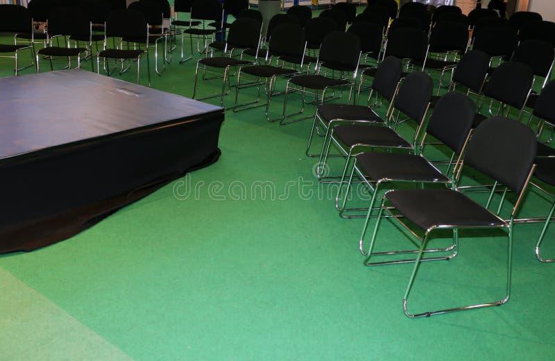 Opróżnia krzesła z małą sceną dla mówcy obrazy royalty free