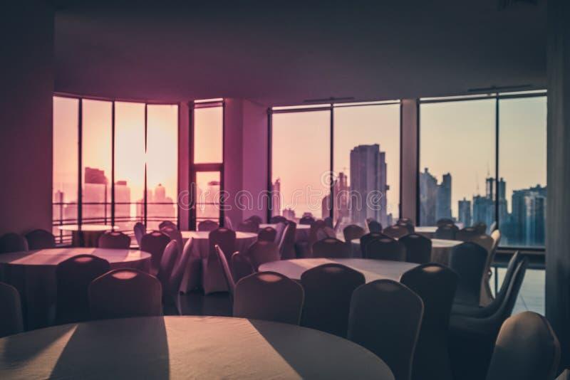 Opróżnia obiadowego stół w pokoju z widokiem nad nowożytnym linia horyzontu podczas fotografia royalty free