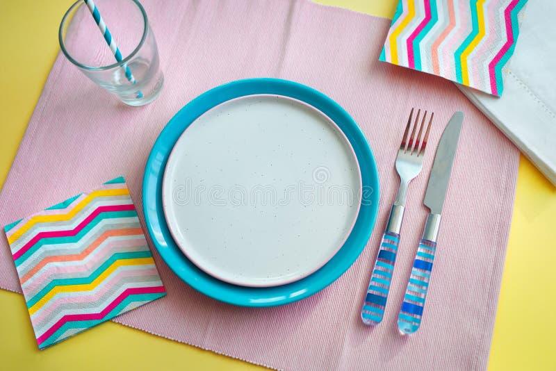 Opróżnia półkowego i błękitnego Cutlery na różowym tle pojęcie narządzanie jeść zdjęcia stock
