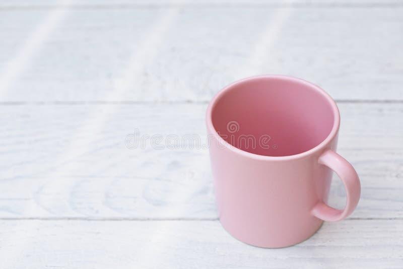 Opróżnia różowego ceramicznego kubek na biel malującym drewnie Przestrze? dla teksta obrazy stock