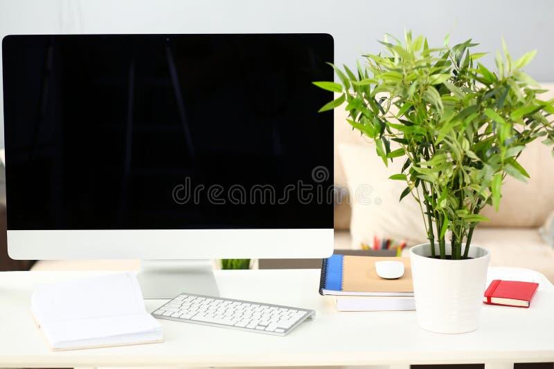 Opróżnia srebnego komputer przy worktable z kanapą w tle fotografia royalty free