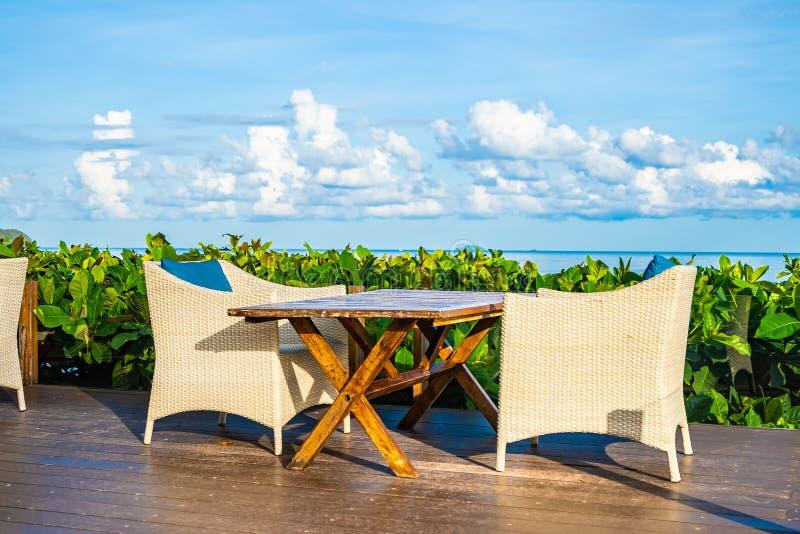 Opróżnia stół i krzesła dla łomotać setu oceanu prawie denną plażę na biel chmury niebieskim niebie fotografia royalty free