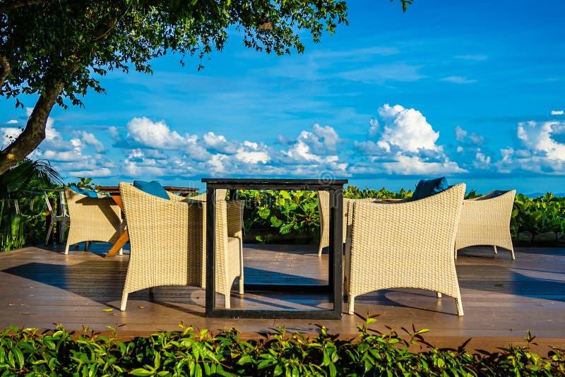 Opróżnia stół i krzesła dla łomotać setu oceanu prawie denną plażę na biel chmury niebieskim niebie zdjęcia stock