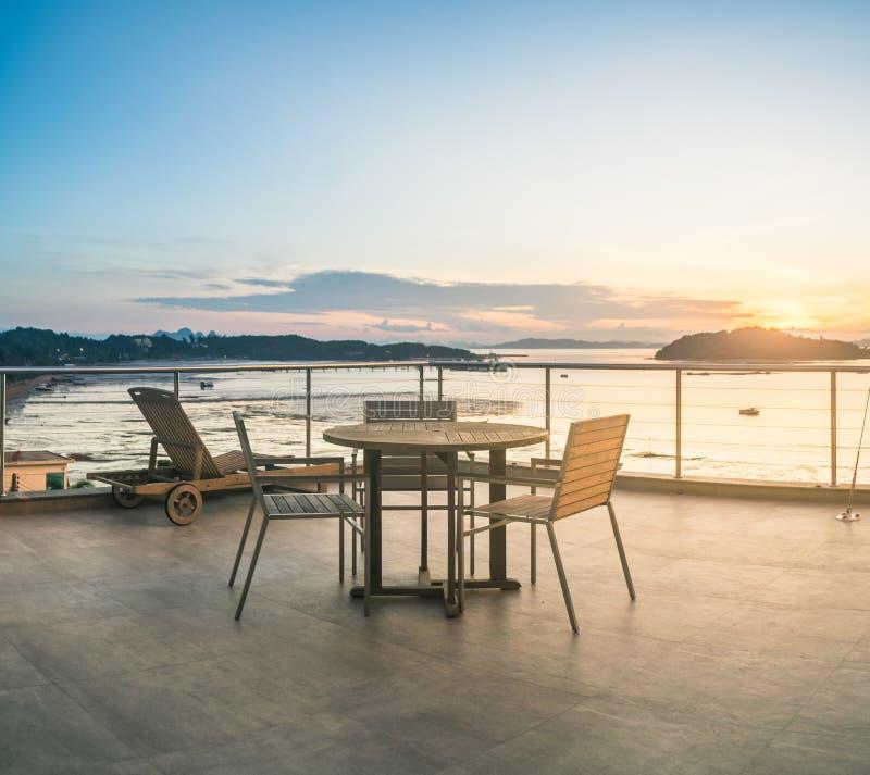 Opróżnia stół i krzesła z wschodu słońca widokiem zdjęcie stock