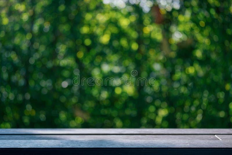 Opróżnia stołowego wierzchołka drewna stół z świeży zielony abstrakt zamazującym tre fotografia stock