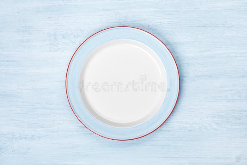 Opróżnia talerza na błękitnym drewnianym stole Odgórny widok z Copyspace obrazy royalty free