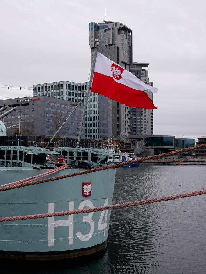 OPR BÅ'yskawica - very famous polish war ship docked in port of Gdynia, Poland - polish white red flag and the gray skyscraper royalty free stock photos