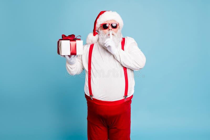 Oprime su secreto. Retrato de divertida grasa concentrada de santa claus con gran abdomen preparar regalo para la espera de la noc imagenes de archivo