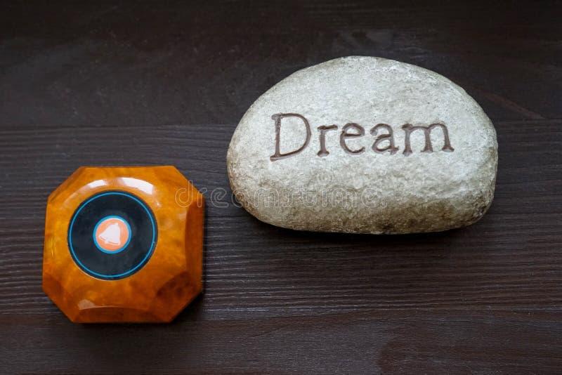 Oproepen de droom Grijze steen met de inschrijvingsdroom op de lijst Dichtbij de kelner van de knoopvraag Concept droom en hoop royalty-vrije stock afbeelding