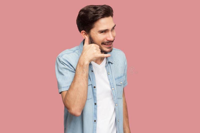 Oproepen me? Portret van de gelukkige knappe gebaarde jonge mens in blauw toevallig stijloverhemd die zich met de hand van het vr royalty-vrije stock foto's