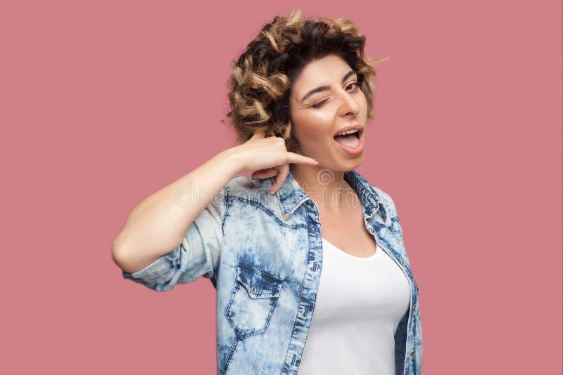 Oproepen me? Portret van grappige jonge vrouw met krullend kapsel in toevallig blauw overhemd die zich met vraaggebaar bevinden e stock foto's