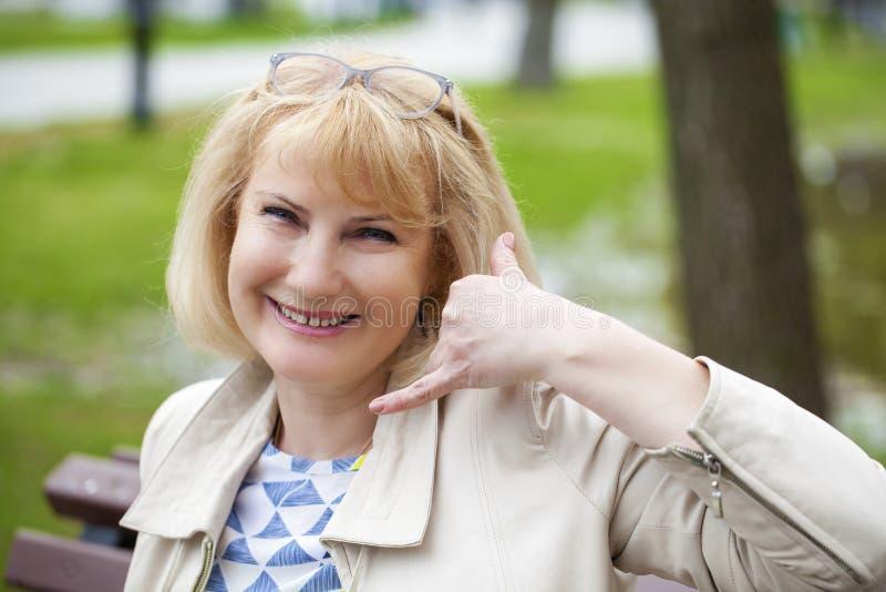 Oproepen me portret van mooie midden oude vrouw in het de zomerpark royalty-vrije stock foto's