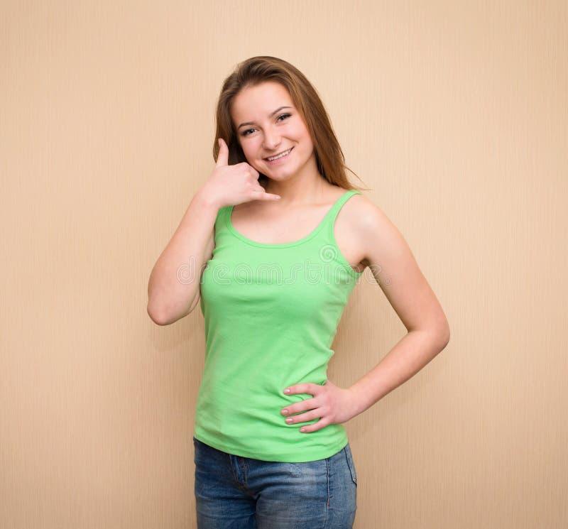 Oproepen me? Vrolijke jonge vrouwen die telefoon teken en het glimlachen gesturing stock afbeelding