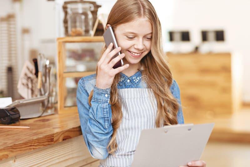 Opromieniona blondynka cieszy się rozmowę telefoniczną w kawiarni zdjęcia royalty free