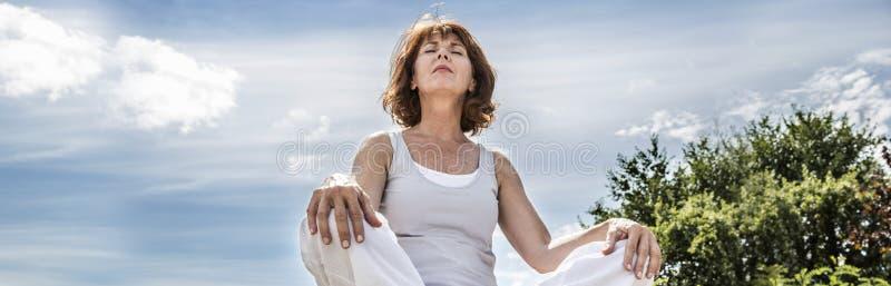 Opromieniona 50s joga kobieta szuka dla sprawy duchowe równowagi, niski kąt zdjęcie royalty free
