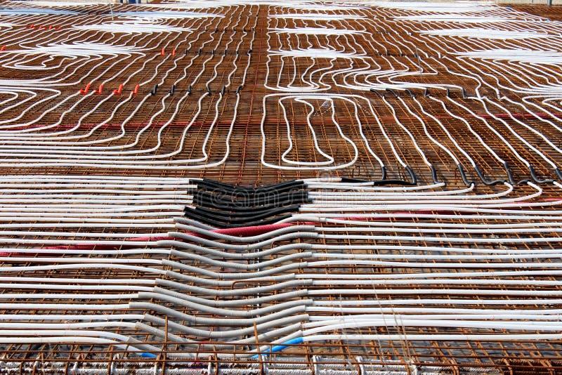 Opromieniony podłogowy ogrzewanie instaluje przy budynek budową z gęsto kłaść plastikowymi wodnymi drymbami na górze rdzewiejący fotografia stock