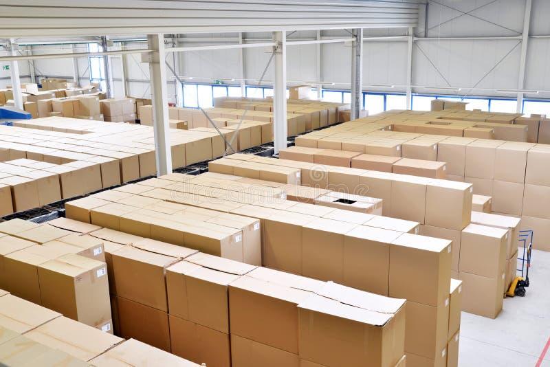 Opslag van kartondozen in een groot pakhuis van industrieel stock afbeeldingen