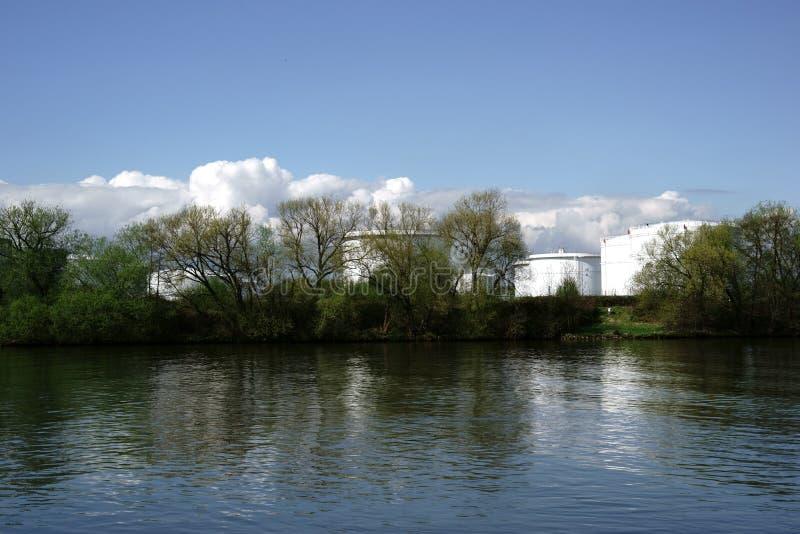 Opslagtanks achter de rivier stock afbeelding
