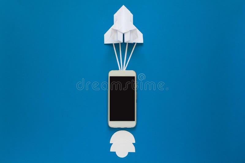 Opstarten of snel verbindingsconcept De lanceringsdocument raket met slimme telefoon op blauwe hemel met wolken stock afbeeldingen