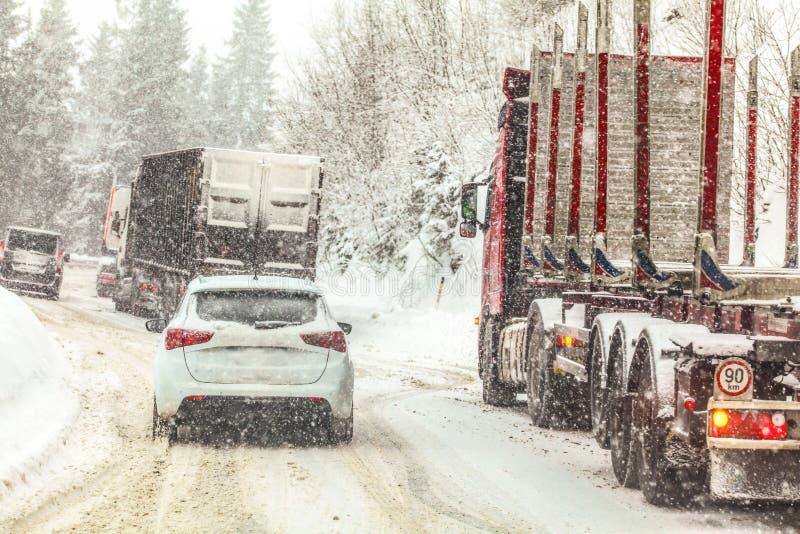 Opstopping, auto's en vrachtwagens die langzaam bij de bergpas van de de winter bosweg tijdens zware sneeuwblizzard alle emblemen royalty-vrije stock afbeeldingen