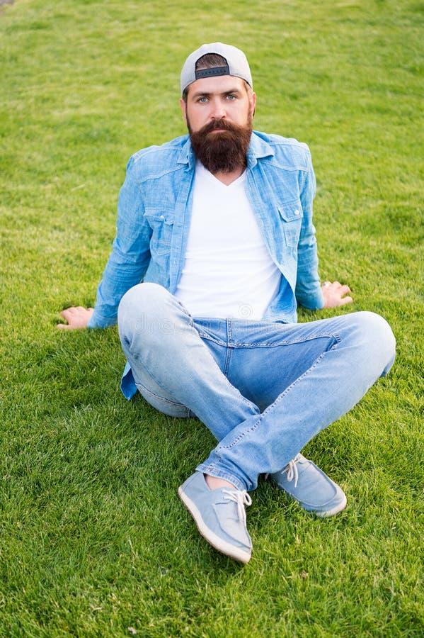 Opti per semplicità sopra vistosità Uomo di modo che si siede sull'erba verde Uomo barbuto nello stile del denim di modo all'aper immagini stock libere da diritti