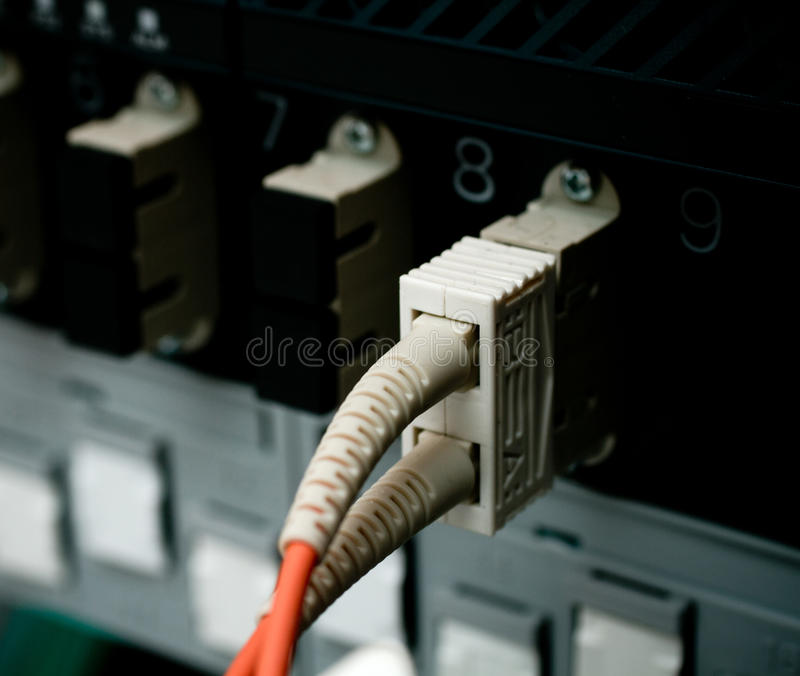 Optic fiber cables connected to a switch stock images