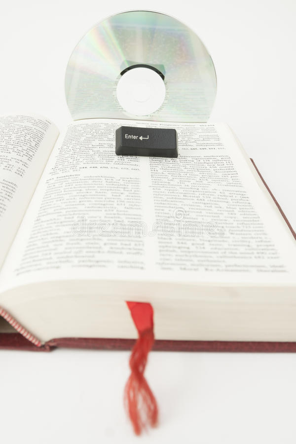 Optical Disc, Enter Key on a Book Page. Optical Disc and Enter key placed on a Book Page stock photography